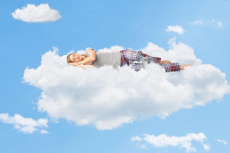 Menina dormindo em uma nuvem no céu azul