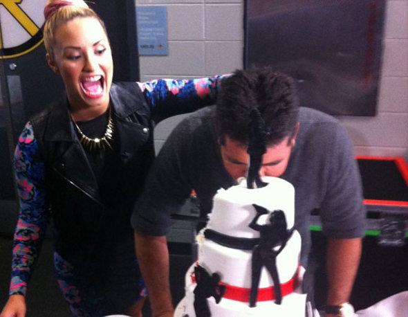 Surpresa! Demi Lovato lambuza de bolo Simon Cowell