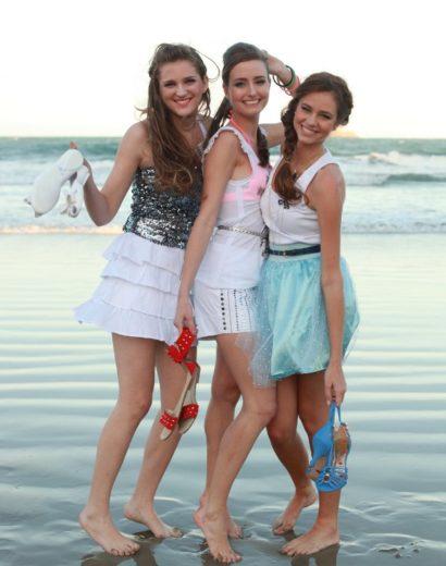 meninas na praia com as pernas de fora