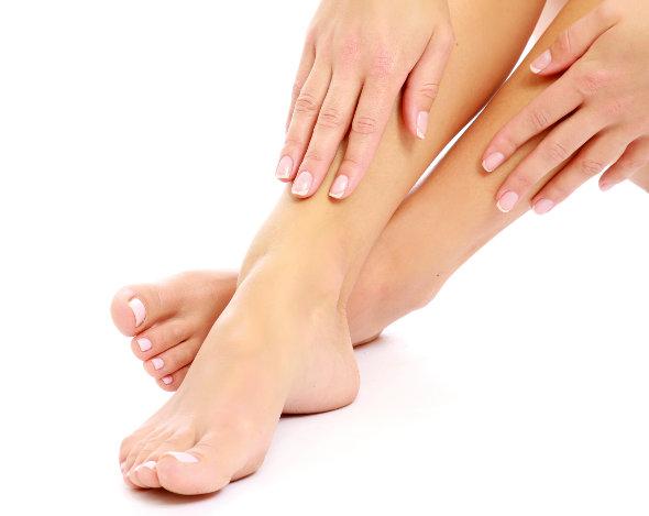 mulher hidratando a perna e os pés