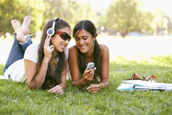 duas meninas ouvindo música e olhando o celular