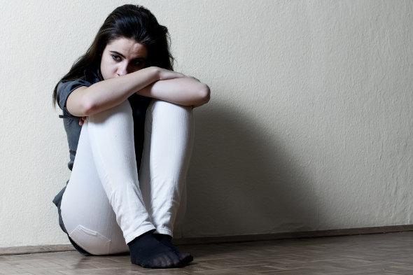 menina sentada com mão no joelho triste