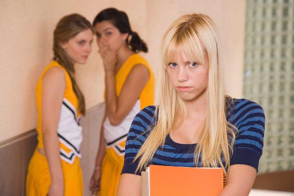 duas meninas fazendo fofoca e uma menina triste