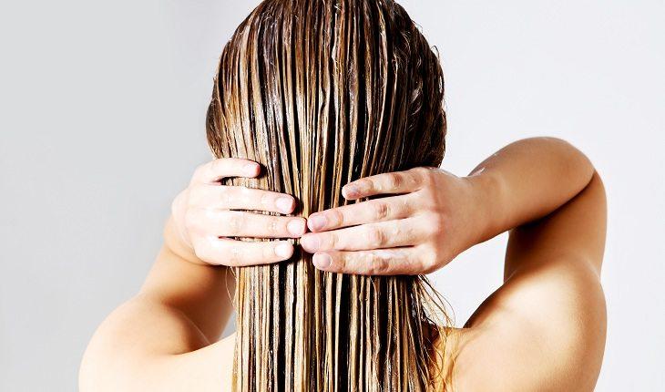 garota passando creme no cabelo