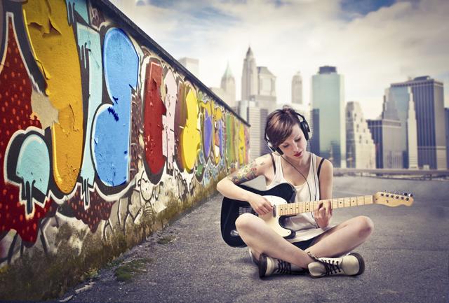 menina sentada tocando guitarra