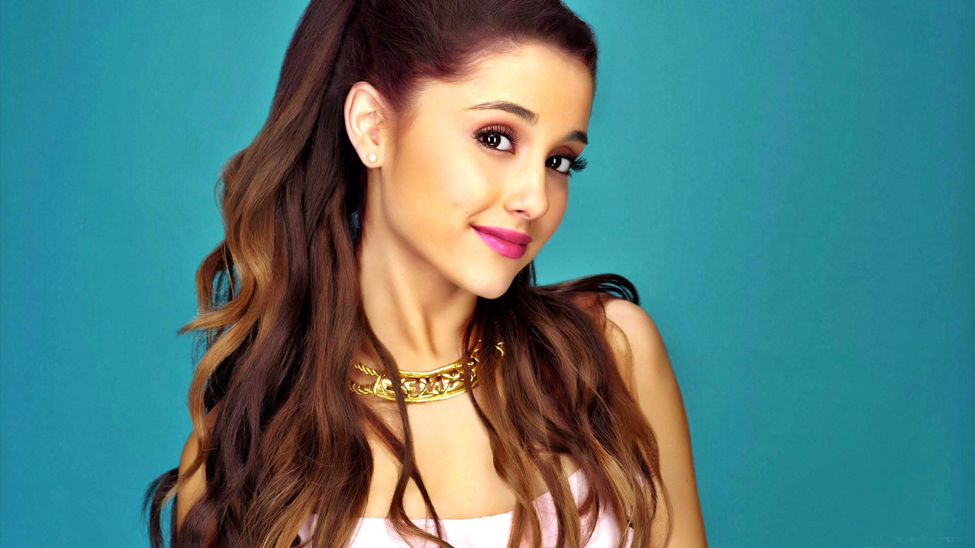Ariana Grande cabelo comprido e preso no fundo azul