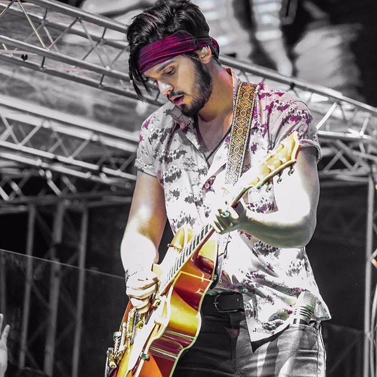Luan Santana tocando violão em show com novo cabelo