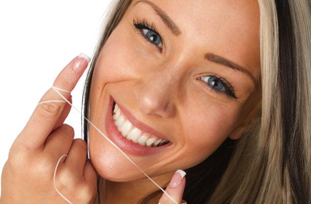 Garota loira passando fio dental