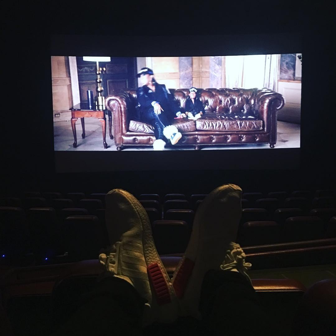 Justin Bieber com os pés na poltrona do cinema