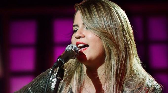 Marília Mendonça cantando em um fundo roxo