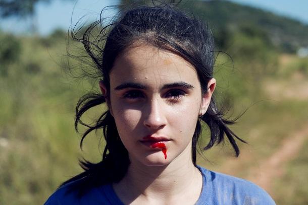 Valentina em cena de Mate-Me Por favor, com a boca sangrando