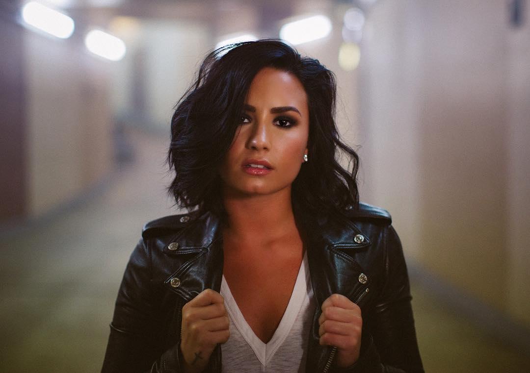 Demi Lovato com cabelo curto e uma jaqueta de couro