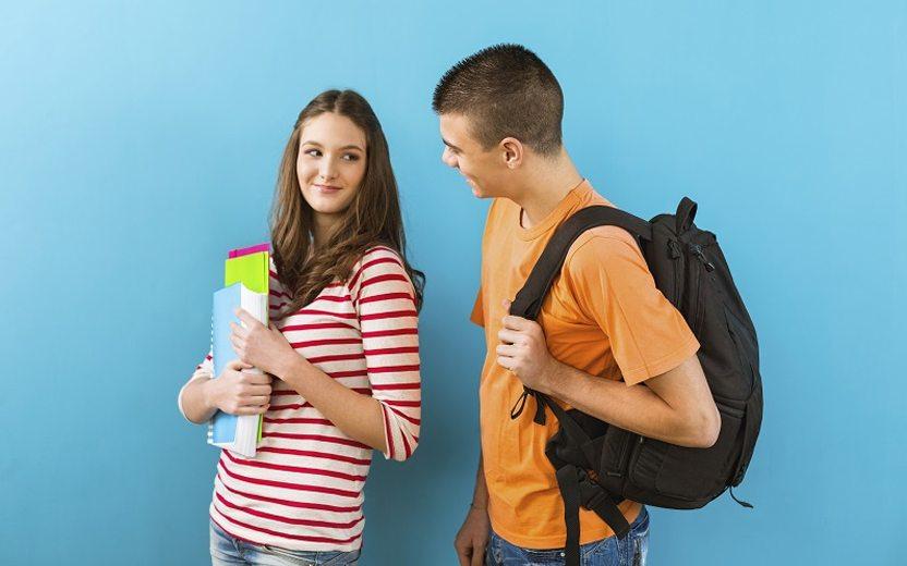 Paquera na volta às aulas: menina e menino com mochilas e cadernos se olhando