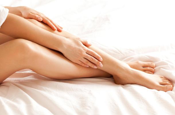 Pernas brancas aplicando creme