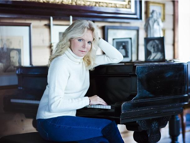 Lucinda Riley, escritora, sentada em um piano