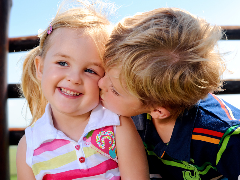 Menininho beijando meninha