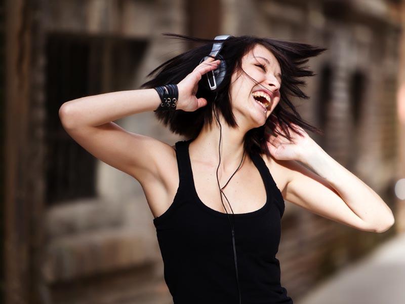 MEnina feliz ouvindo música com fone