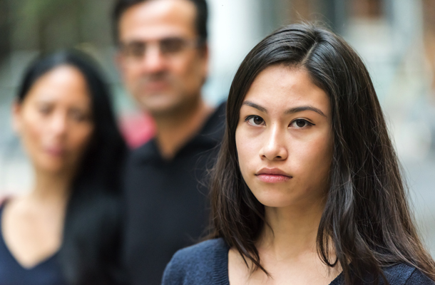 Garota com olhar triste junto com os pais
