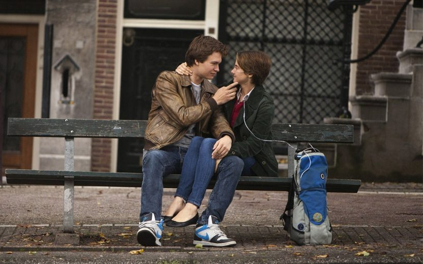 A Culpa é das Estrelas: Hazel e Gus em um banco de parque olhando um para o outro