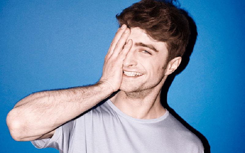 daniel radcliffe com a mão no rosto em um fundo azul