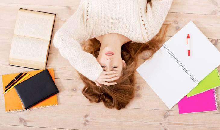 Garota estressada deitada no chão, com mãos na cabeça