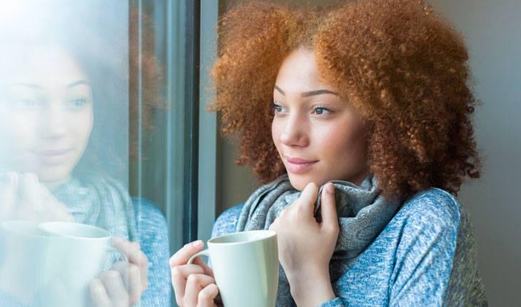 Garota reflexiva olhando a janela