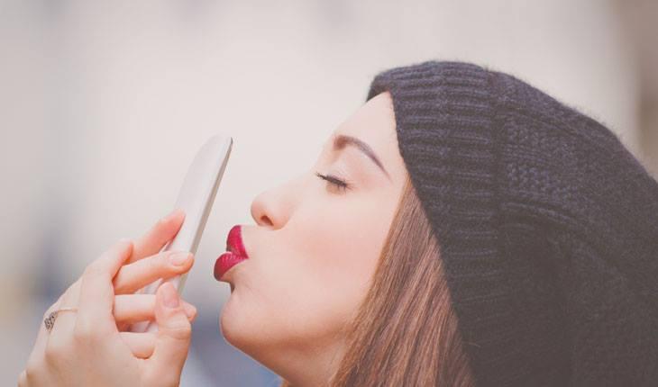 Mulher dando beijo em celular