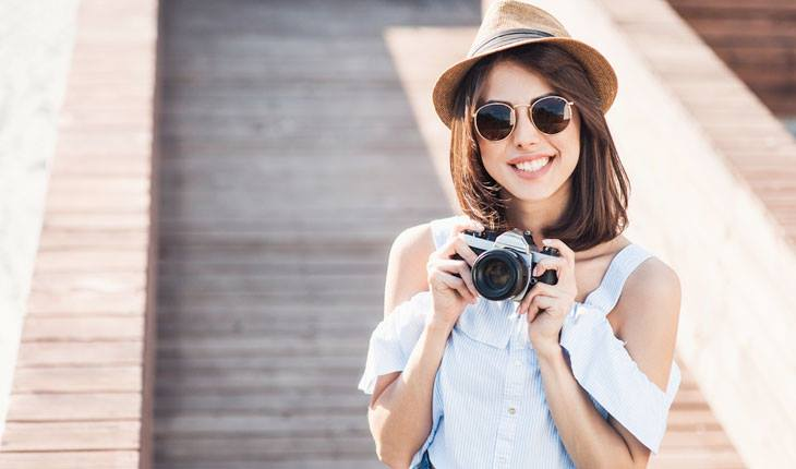 Menina sorrindo com câmera na mão