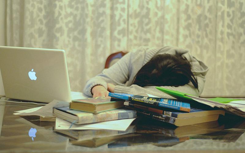 menina deitada em cima da mesa estudando para enem