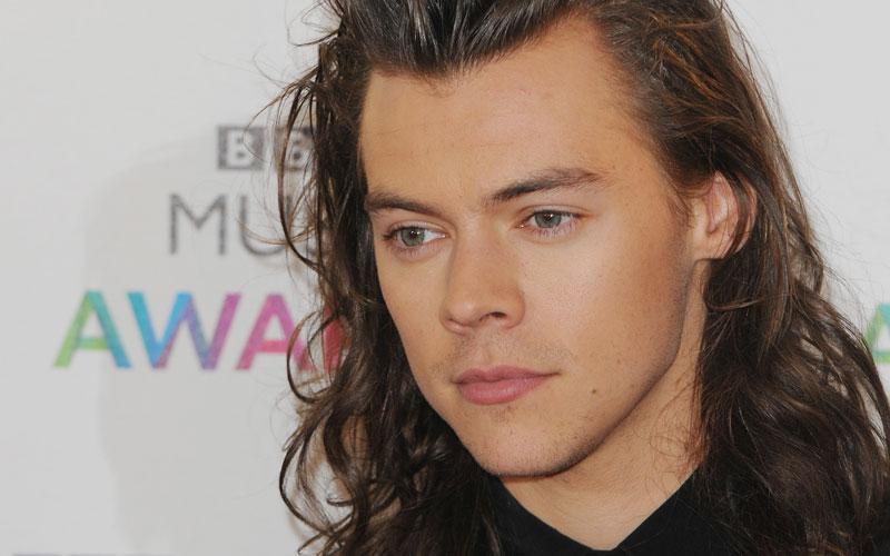 Harry Styles com cabelo comprido em evento com One Direction