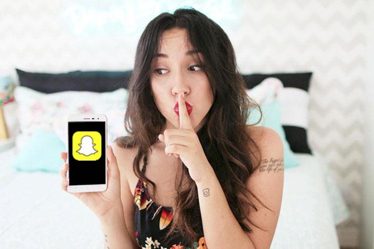 bruna vieira fazendo sinal de 'sh' e segurando um celular com snapchat