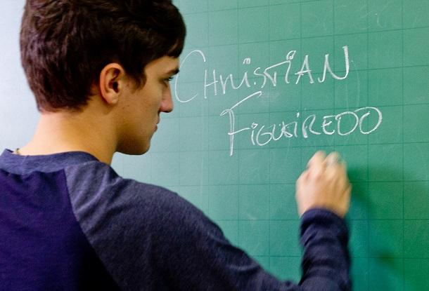 Christian escrevendo seu nome numa lousa
