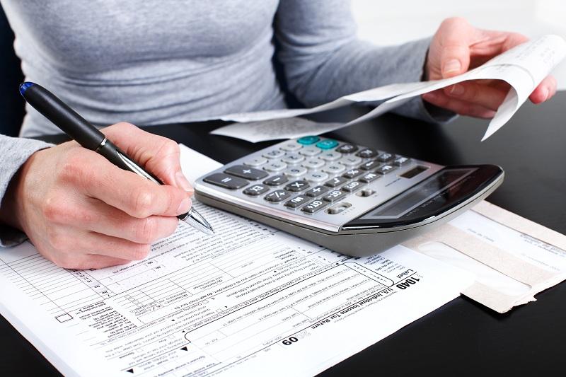 moça fazendo contas com papel, caneta e calculadora