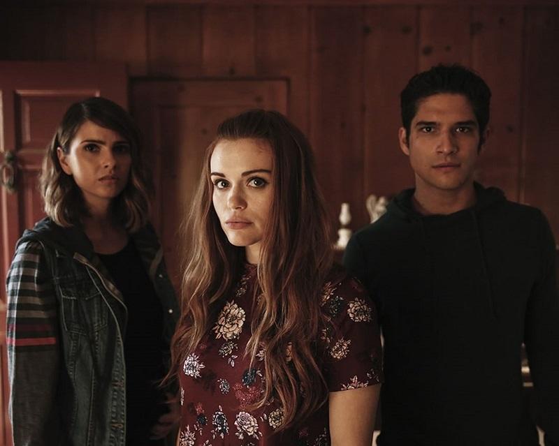 Três atores da série Teen Wolf em fundo vermelho