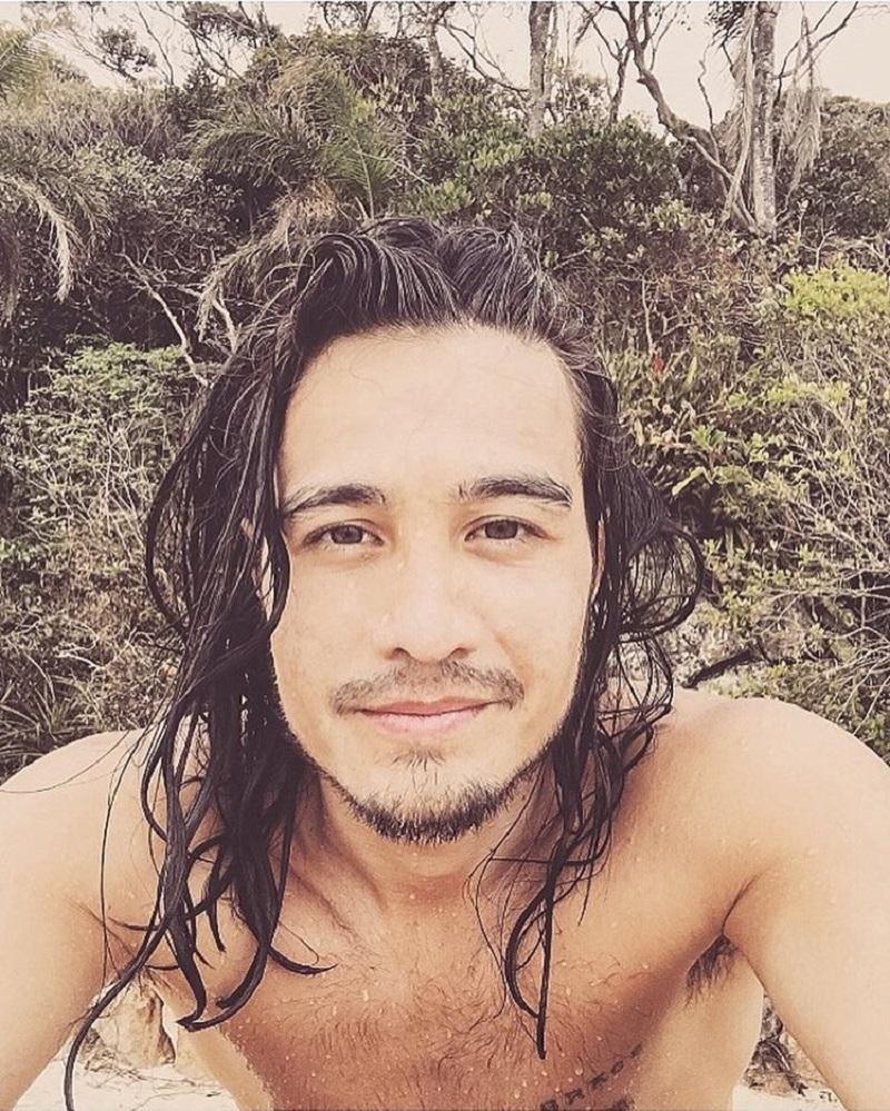 Tiago Iorc com leve sorriso, de cabelo molhado