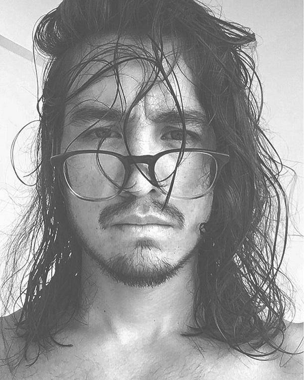 Tiago Iorc de óculos e de cabelo molhando em foto preta e branca