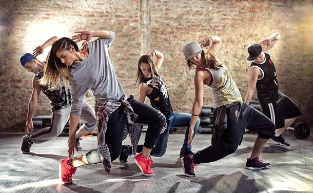 Jovens com roupa fitness ensaiando uma dança