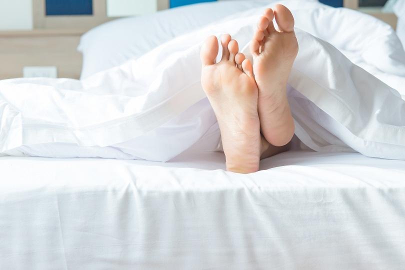 Pés de uma garota deitada em uma cama com lençóis brancos