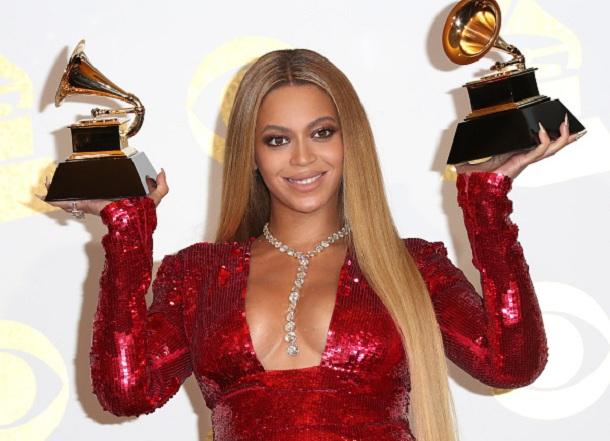 Beyoncé no Grammy com vestido vermelho segurando dois prêmios