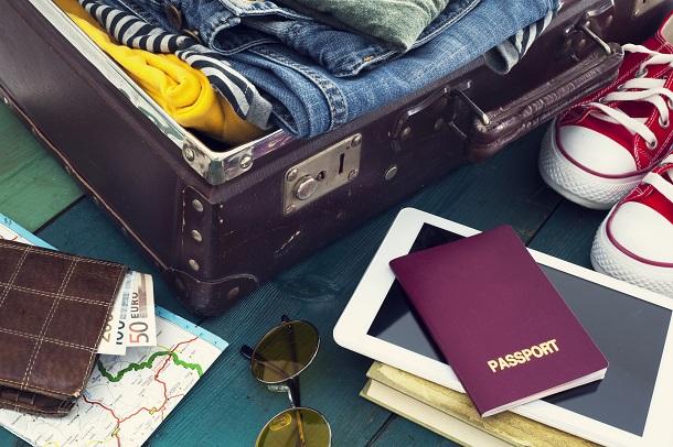 Mala aberta com calças, camisa, óculos, tênis e passaporte