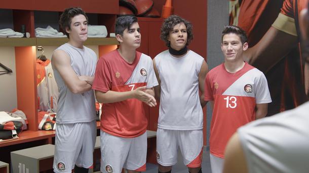 Quatro meninos em um vestiário com uniforme de futebol