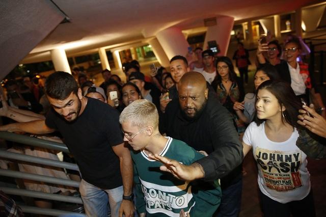Justin Bieber em restaurante na Zona Sul do Rio acompanhado de seguranças e rodeado por fãs.