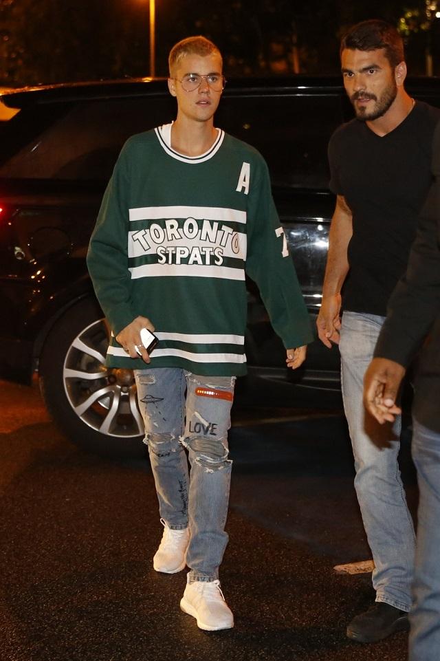 Justin Bieber caminha com segurança próximo ao restaurante em que foi jantar no Rio.