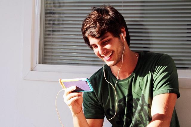 Bruno Guedes, ator de malhação, com um celular na mão e rosto com aspecto emocionado