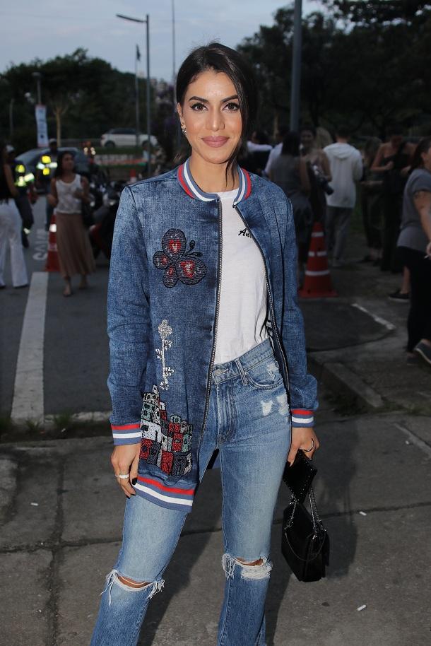 Camila Coelho vestindo calça jeans rasgada e jaqueta jeans com bordados no São Paulo Fashion Week