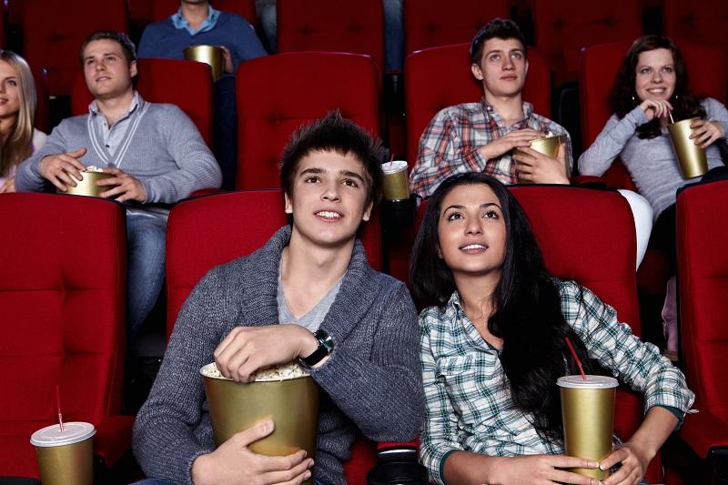Casal comendo pipoca no cinema
