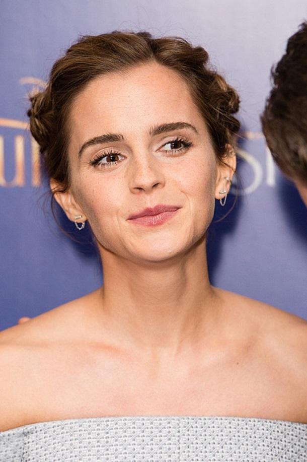 Emma Watson com cabelo em coque e sorriso sem mostrar os dentes