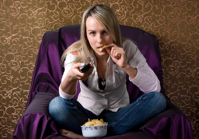 Menina assistindo a series e comendo com o controle na mão