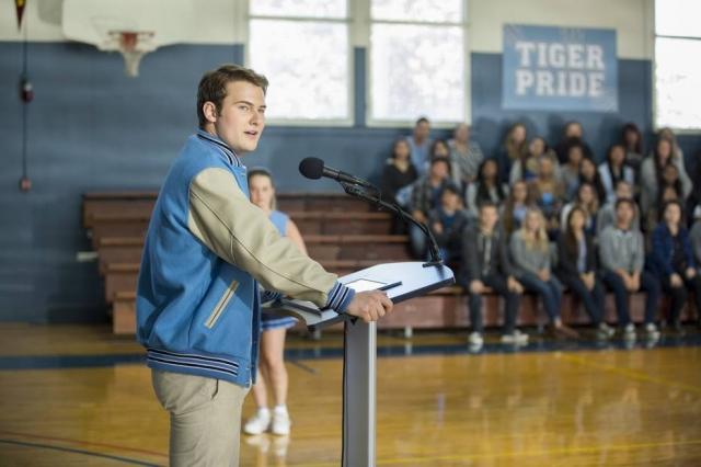 Bryce Walker, personagem de 13 Reasons Why, falando em um auditório.