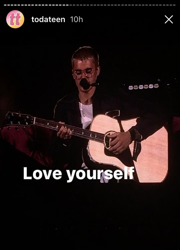 Justin sentado no palco com violão